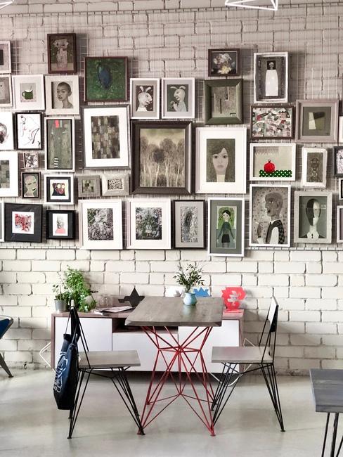 Wanddecoratie met fotolijsten boven de eettafel en stoelen in art-deco stijl.
