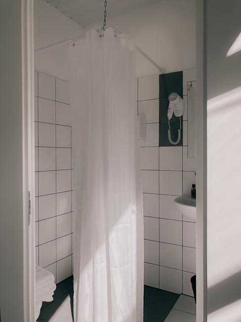 Witte badkamer met vierkante tegels met een wit douchegordijn