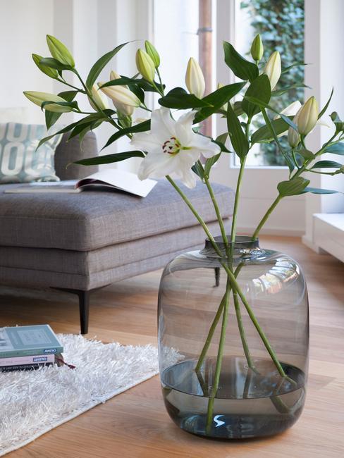 Transparante glazen vaas met bloemen in woonkamer in scandi stijl