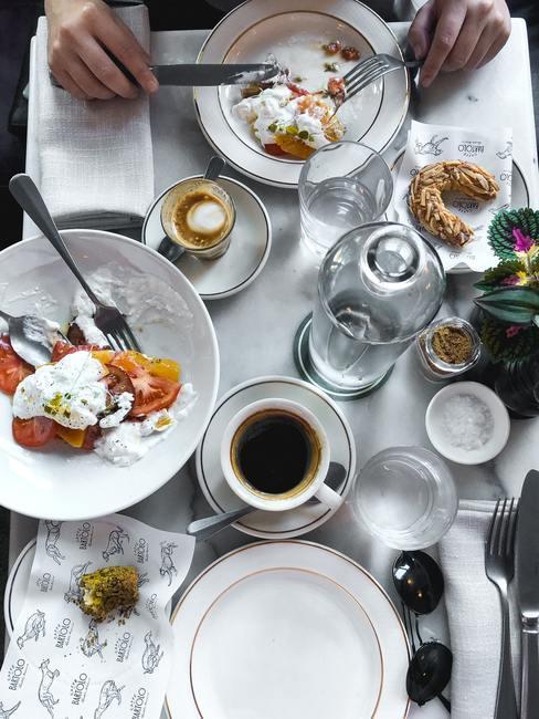 Gedekte tafel met zilveren bestek en koffie in kopjes