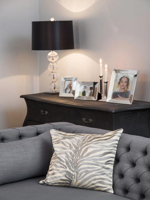 Bank reinigen: Grijze bank met sierkussen, donker houten dressoir met decoratieve zwarte lamp, kandelaars en fotolijst