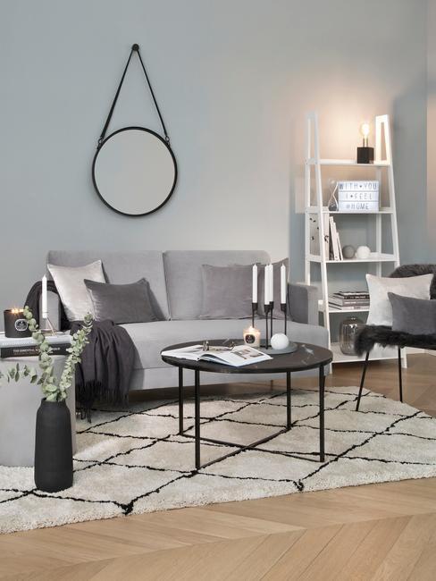 Een grijze zitbank naast zwarte bijzettafel op het vloerkleed en donkere vaas met bloemen en spiegal aan de wand