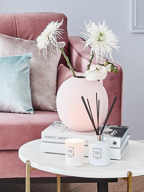 Close-op roze zitbank met sierkussens en witte bijzettafel met koffietafelboek en roze vaas met bloemen en geurkaarsen