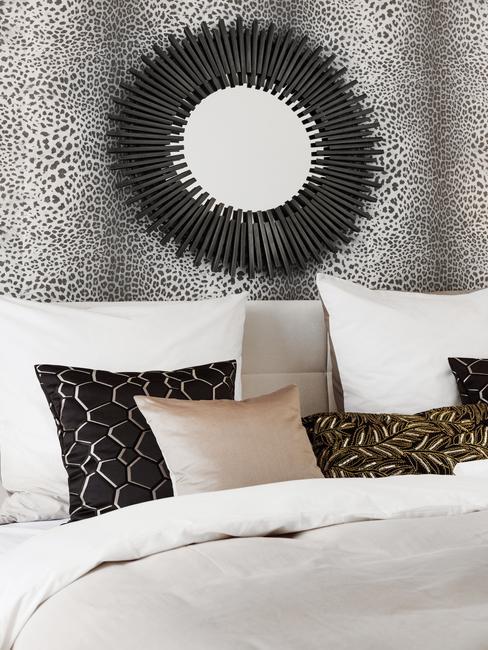 Luipaardprint behang met een enorme spiegel en een bed bekleed met wit linnen en sierkussens