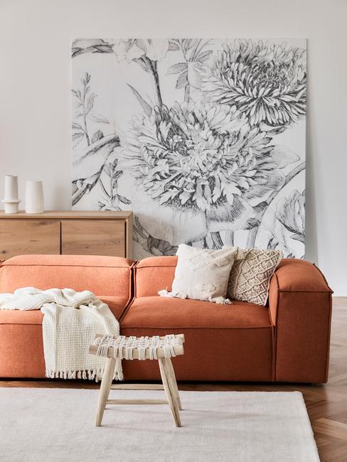 Woonkamer met een oranje bank, een houten tafel en een dressoir.