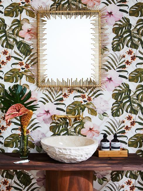 Behang met exotische print met spiegel en accessoires op een houten dressoir
