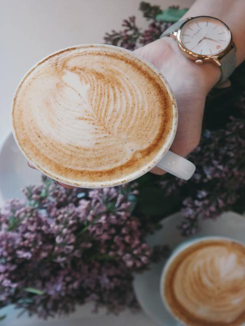 Decoratie met bloemen op tafel en vrouw met koffie in haar hand