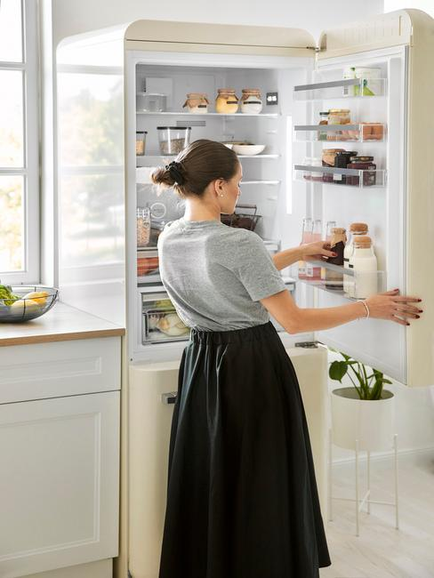 vrouw voor een witte koelkast