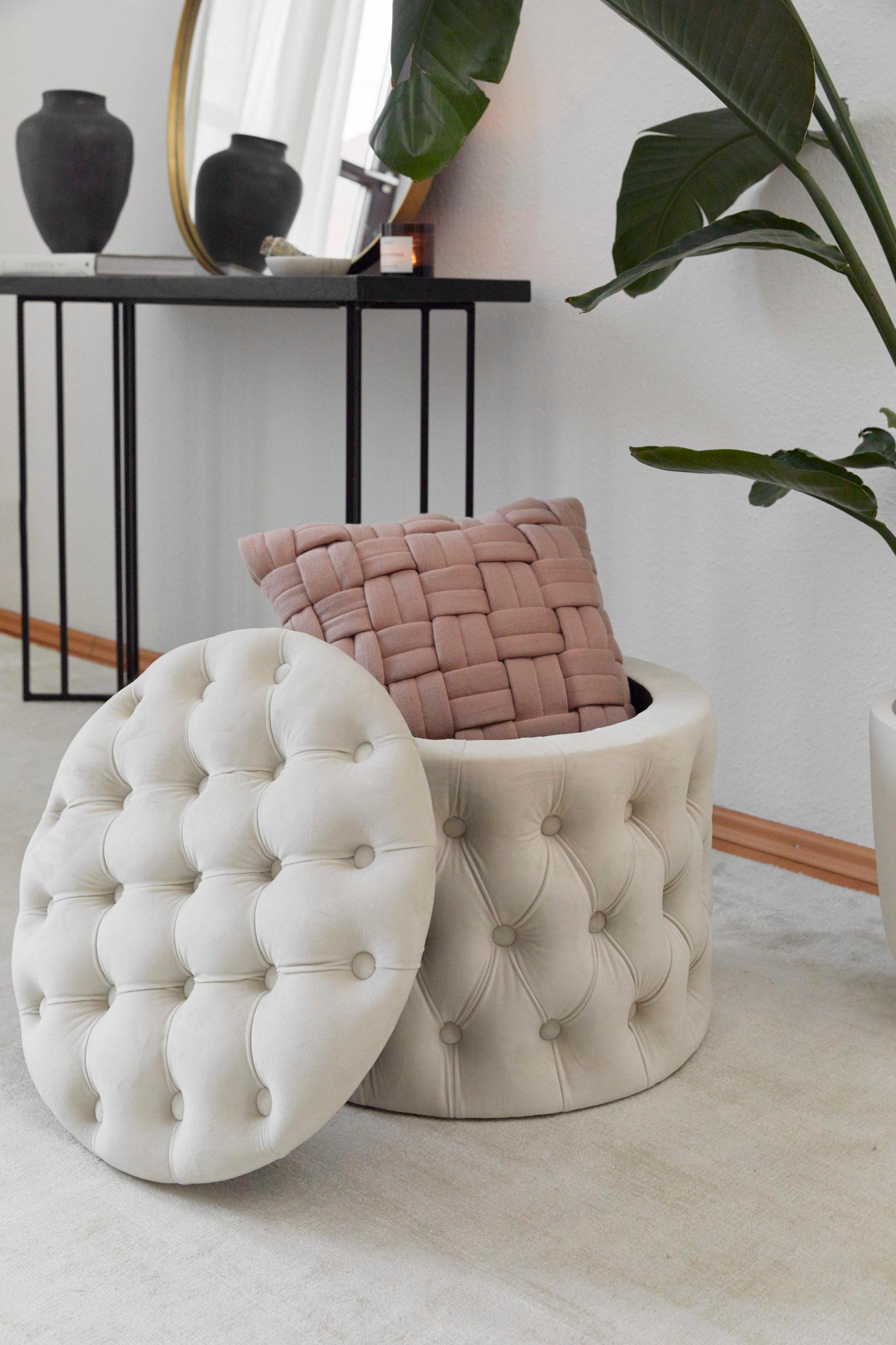 witte poef met roze kussen en groene plant