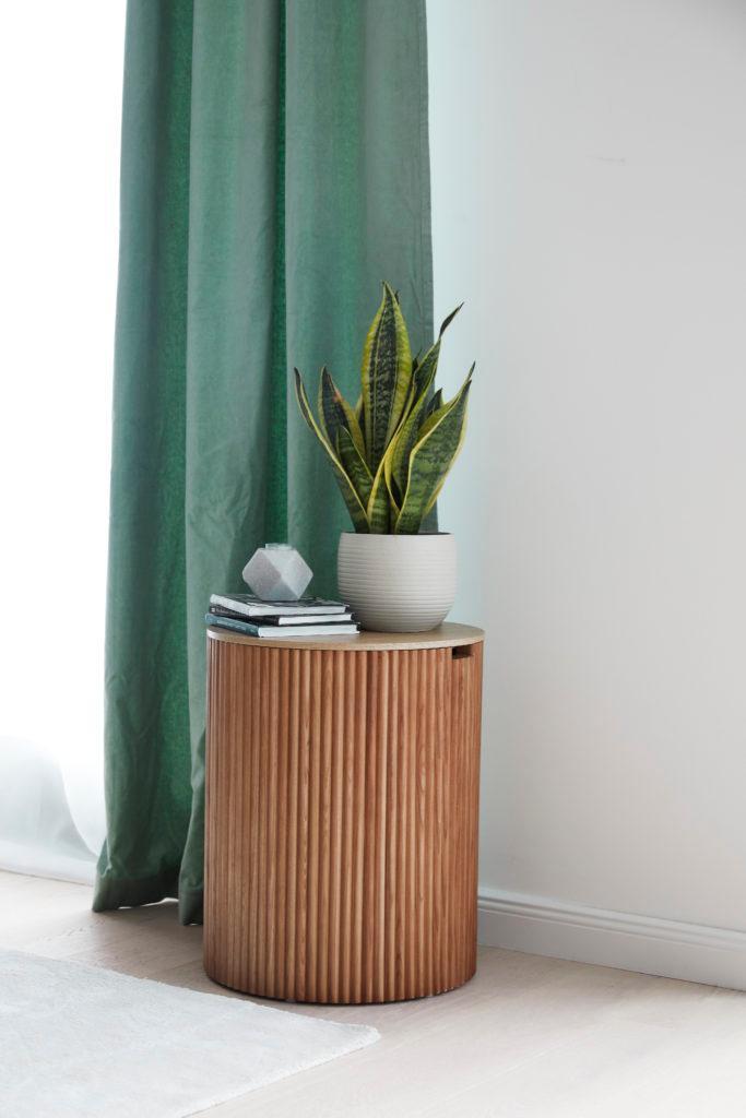 groene gordijnen met houten bijzettafel en plant in pot