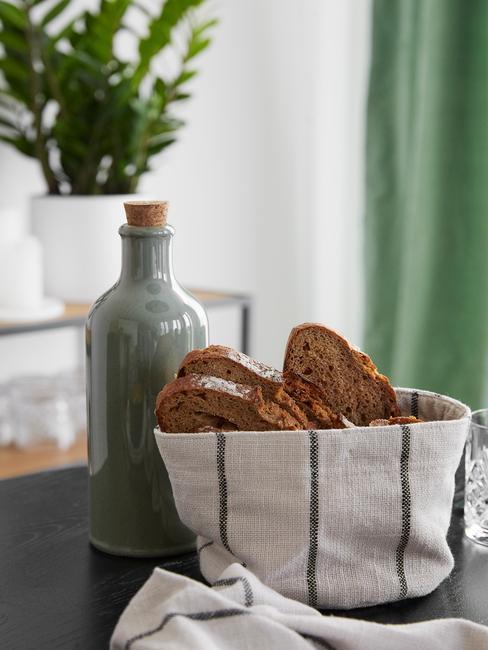 Groene olijflolie fles met stoffen gestreepte broodman op eettafel