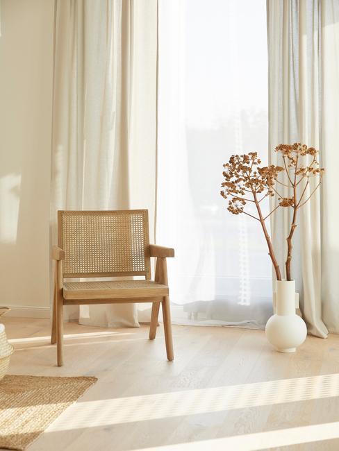 rotan armleunstoel in woonkamer met witte ronde vaas en droogbloem