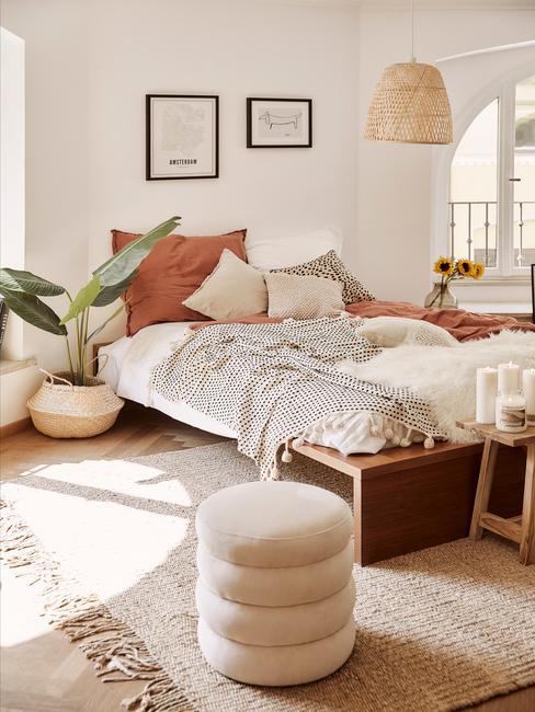 Landelijke slaapkamer met groot bed en fluwelen poef