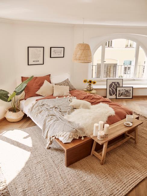Landelijke slaapkamer met groot bed en houten zitbank