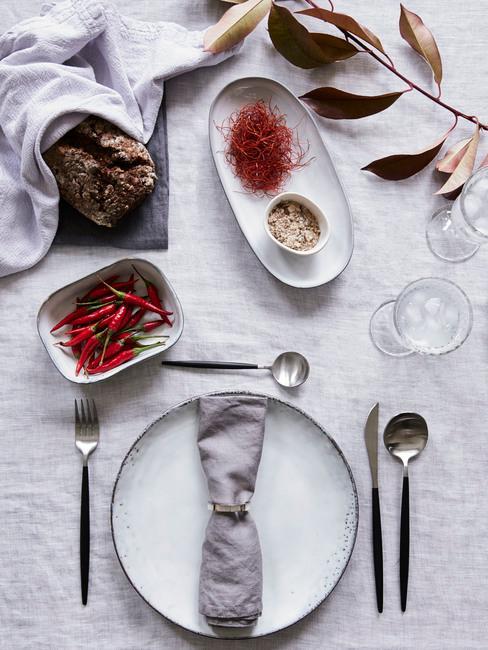 Tafel met een witte tafelkleed en servies en voorgerechten