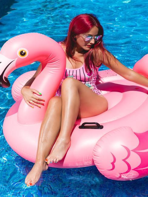 Vrouw in het opblaasbare roze flamingobad