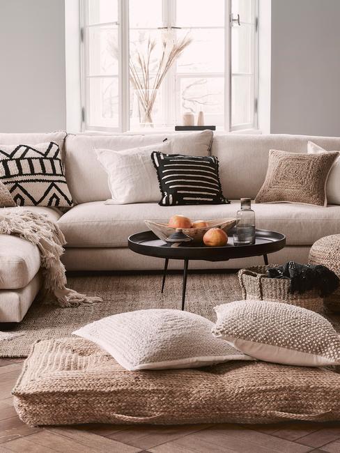 cocoone: een comfortabele beige bank met sierkussens naast een houten salontafel met kaarsen