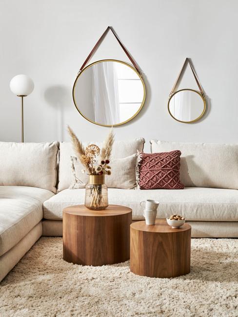 Woonkamer in boho stijl met decoratieve spiegels en comfortabele zitbank met sierkussens naast houten salontafels