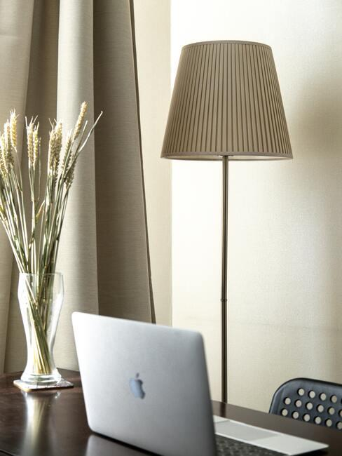 Vaas op bureau naast een beige vloerlamp