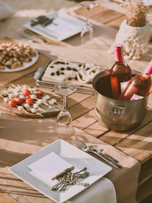 flessen rose en snacks op houten tafel