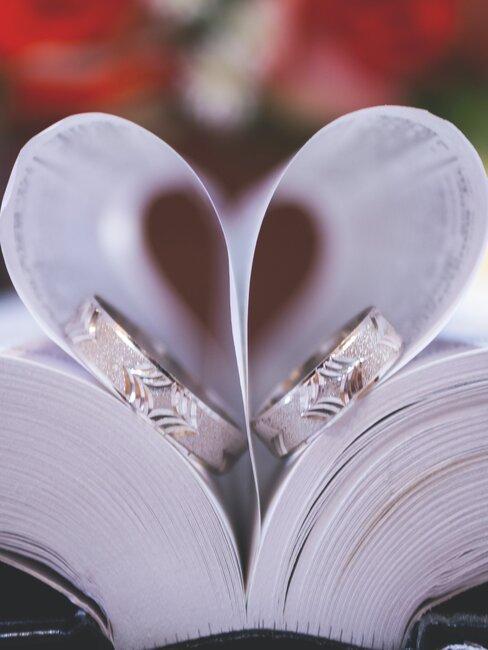 boek met bladzijdes gevouwen in een hart met twee trouwringen