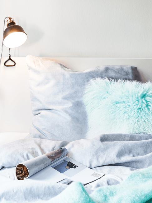 Blauw beddengoed in wit bed met lamp