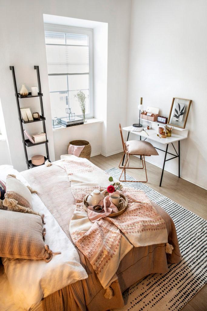 Beige beddengoed en decoratieve ladder in kleine witter ruimte