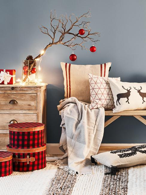 Sinterklaas decoratie met kussens en plaid op houten zitbank naast houten commode met verlichting