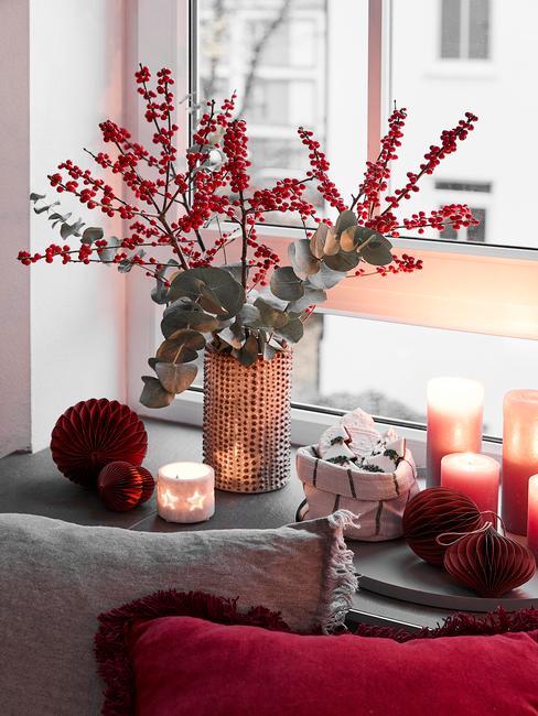 Het raam is versierd met een vaas met bloemen, kaarsen en lantaarns