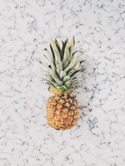 Ananas op een wit-grijs marmeren blad