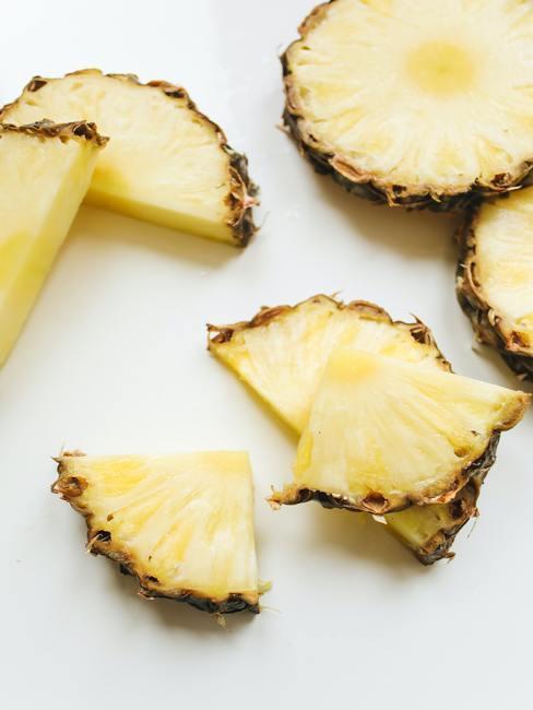 Gesneden stukjes ananas decoratie op een witte gladde blad
