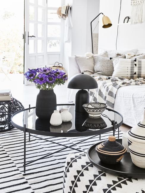 Glazen salontafel in zwart met zwarte vazen met bloemen