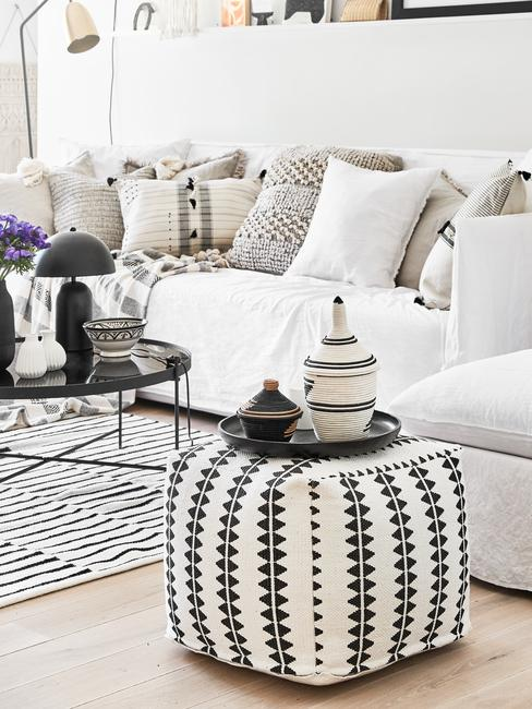 Verlichting woonkamer: Woonkamer in wit met zitbank in creme en sierkussens naast een fluwelen fauteuil in lichtblauw