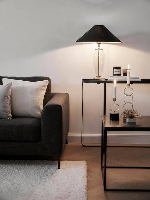 Verlichting woonkamer: Moderne woonkamer met zitbank in zwart en sierkussens in donkere kleuren met hanglamp in goud en sidetable in zwart met zwarte tafellamp