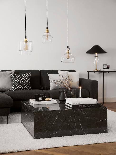 Comfortabele zitbank in zwart en sierkussens in donkere kleuren met hanglamp in goud