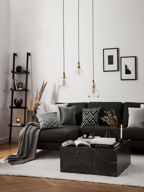 Moderne ruimte met zitbank in zwart en sierkussens in donkere kleuren met hanglamp in goud
