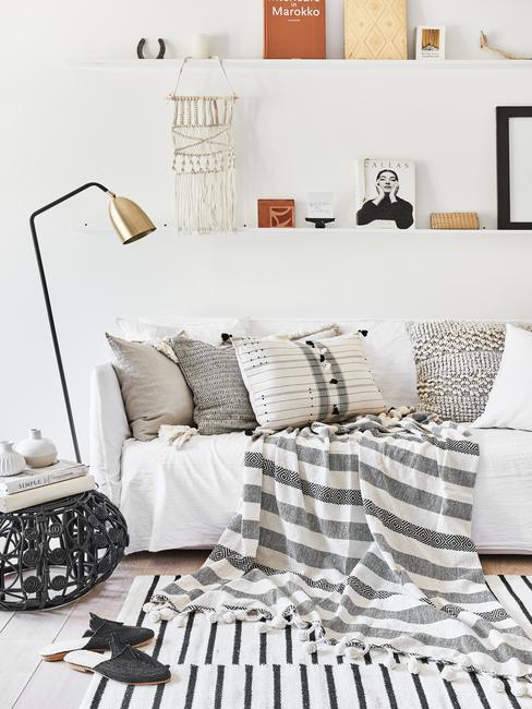 Woonkamer in wit met zitbank in creme en sierkussens naast een fluwelen fauteuil in lichtblauw