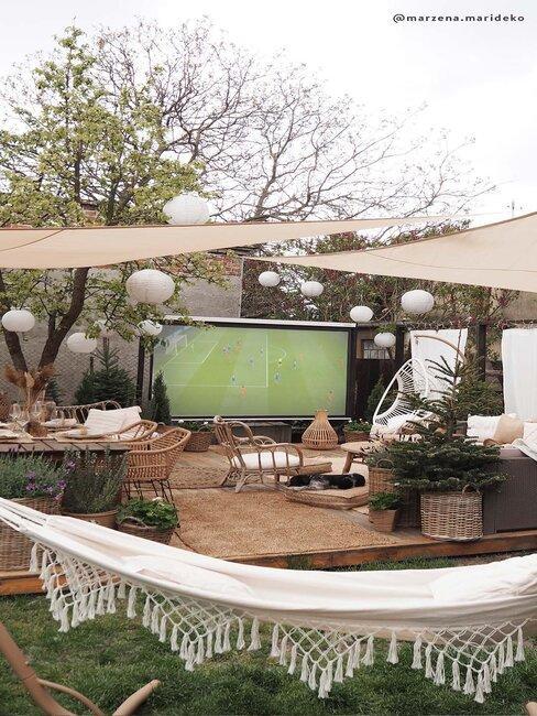 voetbal wedstrijd op een projectiescherm in een tuin