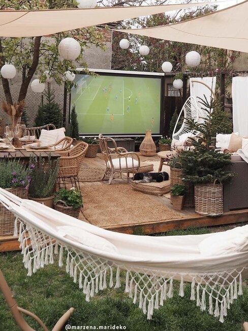 voetbalwedstrijd geprojecteerd op een scherm in de tuin
