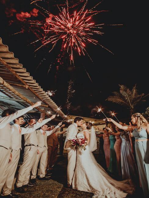 bruidspaar met gasten om hun heen en rood vuurwerk
