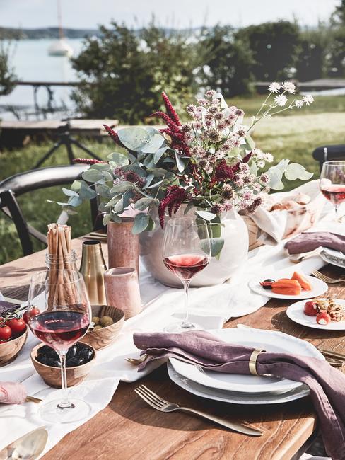 Gedekte tafel met vaas met bloemen en rode wijn