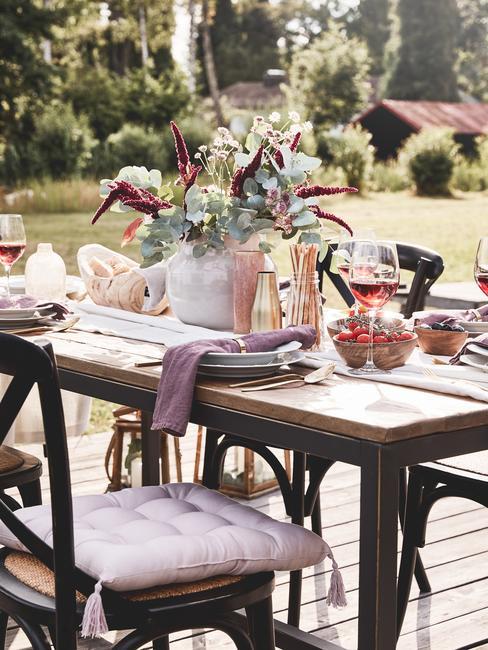 Gedekte tafel met vaas met bloemen en rode wijn in glazen