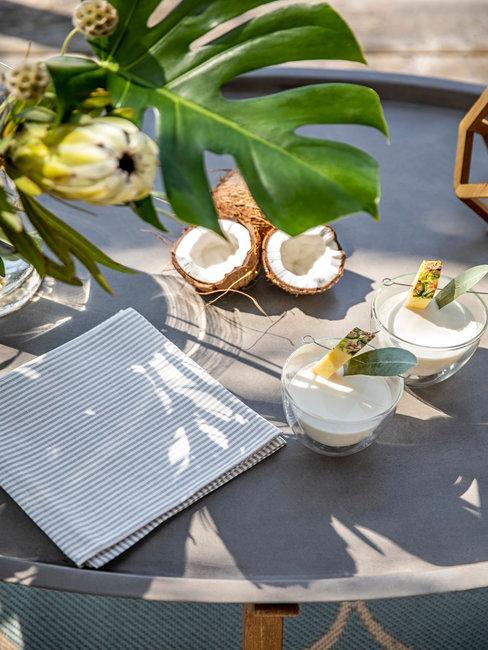 Kokosnoot en cocktails met palmbladeren buiten op bijsettafel