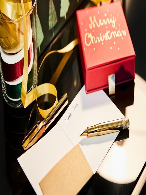 Kerstkaarten maken: pen en een vel papier naast de geschenkdoos