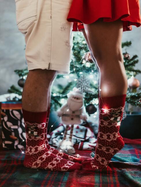 paar in kerstsokken op de achtergrond van de kerstboom