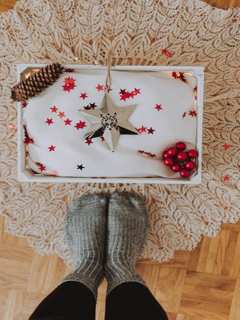 Pakjesavond: vrouw in grijze sokken op een zacht wollen tapijt