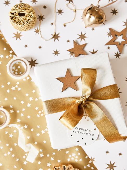 Klassiek verpakt cadeau in wit papier en een gouden lint