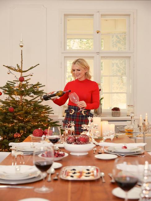 Gedekte tafel met serviesset en bloemen naast kerstboom