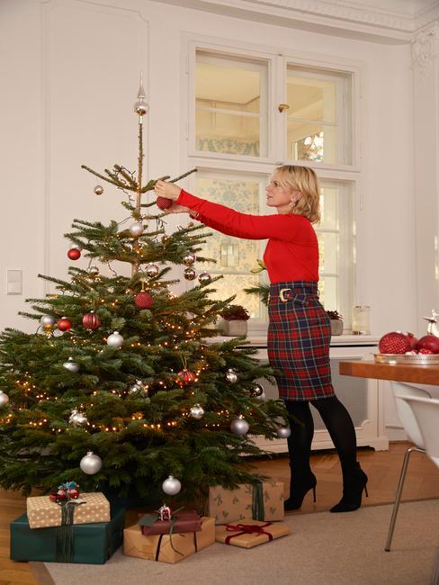 Een vrouw die een kerstboom aankleedt