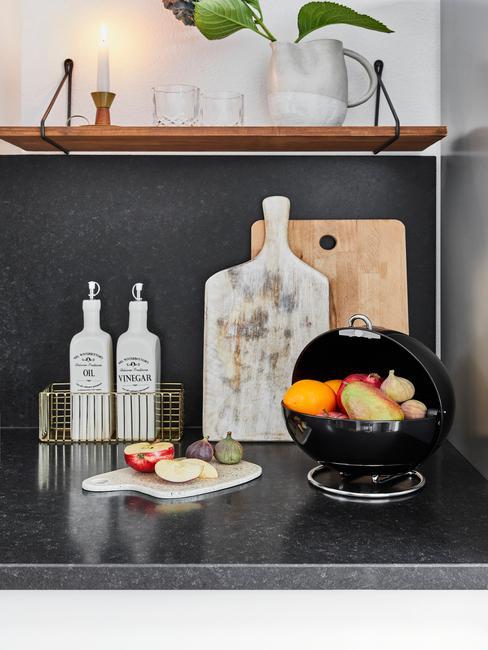 Open keuken met zwart aanrecht en fruitmand